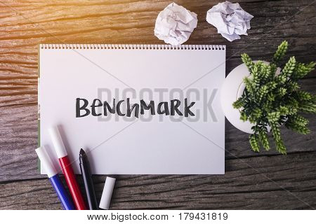 Benchmark Word With Notepad And Green Plant On Wooden Background.