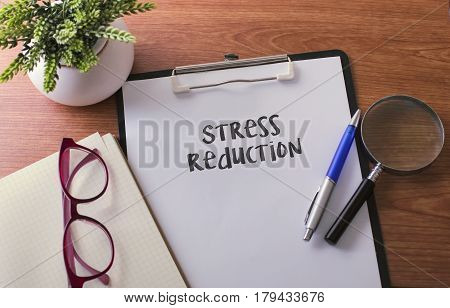 Stress Reduction Word On Paper With Glass Ballpen And Green Plant.