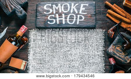 Frame of smoking pipes, cigars, tobacco and brandy bottles. Western style. Background of burlap on dark wood desk. Wooden signboard with text 'Smoke shop'. Top view