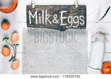 White wood background of milk and egg showcase. Bottle and pot of milk and eggs in a row with green twig. Rustic style. Wooden signboard with text 'Milk and eggs' as a title. Top view