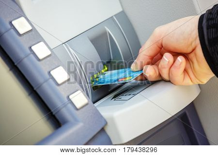 Paris France - October 08 2015: young woman inserting a credit card to ATM