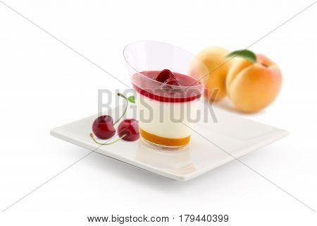 Cherry peach panna cotta on white plate