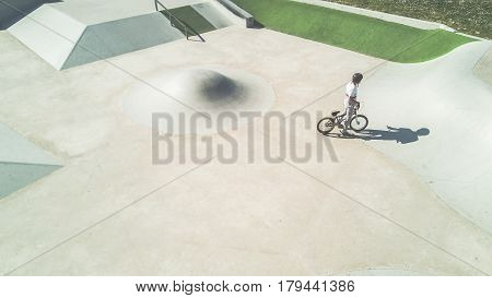 Top minimal view of bmx biker training in skate park outdoor - Young man performing tricks with special bicycle - Focus on man - Extreme sport concept - Opposite rule of thirds - Cinematic warm filter