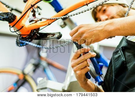 Bearded bicycle mechanic doing his professional work in workshop - Young trendy man checking bike chain inside superbikes laboratory - Repairing concept - Focus on bottom hand - Warm filter