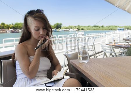 young  girl writing  in a caffe on a sunny summer day