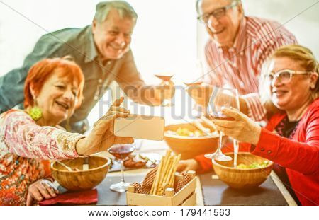 Senior couples taking selfie at home toasting red wine and eating lunch meal - Old friends having fun with new trends technology - Joyful elderly lifestyle concept - Focus on phone hand - Warm filter