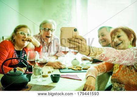 Group of senior people making snapshot selfie with instant camera - Mature happy couples having fun at dinner inside house toasting tea,coffee and red wine - Vintage warm filter - Focus on camera hand