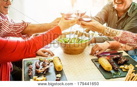 Senior friends cheering with red wine at barbecue lunch indoor - Old people laughing and eating bbq meat with vegetables corn cobs and salad - Focus on bottom hands glasses - Warm contrast filter