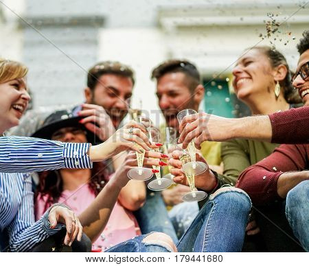 Happy friends cheering with champagne and making party outdoor - Young students celebrating drinking and laughing - Loud fest loudconcept - Main focus on right man hand - Warm filter