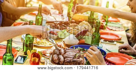 Happy friends eating barbecue meat outdoor in city park on summer time - Young people having fun drinking bear at bbq party - Friendship and food concept - Focus on sausages - Warm contrast filter