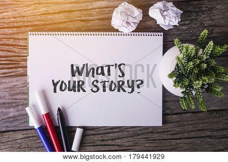 What's Your Story Word With Notepad And Green Plant On Wooden Background.