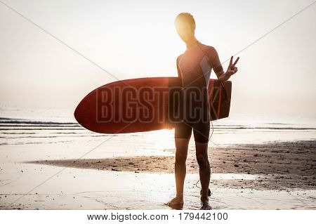 Silhouette of surfer making peace symbol at sunrise outdoor - Young man standing on the beach ready for surfing in Australia - Extreme sport concept - Warm contrast filter
