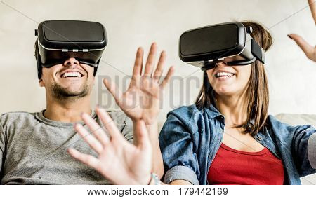 Young couple having fun with virtual reality goggles headset glasses - Happy people playing game with new trends technology - Future concept - Focus on woman headset - Warm contrast filter