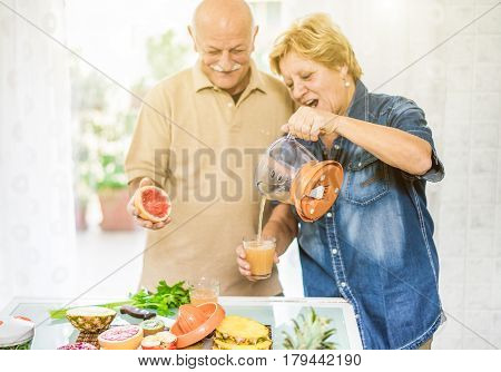Happy senior couple preparing healthy vegetarian breakfast with fruits and vegetables - Old cheerful people making fresh orange juice - Health and bio concept - Focus on woman right hand - Warm filter
