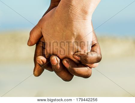 Diverse culture and race couple hands in love romantic moments outdoor - Black man and white woman in tender situatiation against racism - Soft focus on bottom finger - Warm filter
