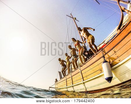 Young people diving from sailing boat into the sea - Happy friends having fun in summer party day - Vacation and friendship concept - Soft focus on right man - Fisheye lens distortion