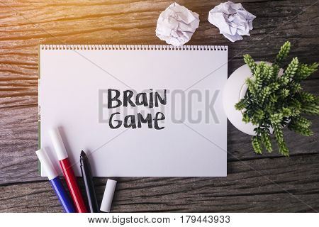 Brain Game Word With Notepad And Green Plant On Wooden Background.