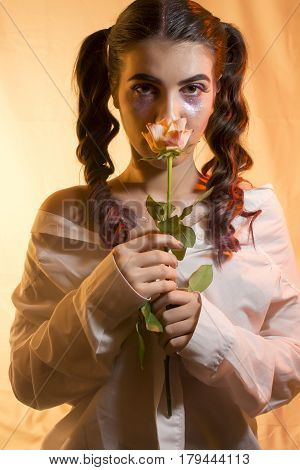Young girl with artistic make up and yellow rose