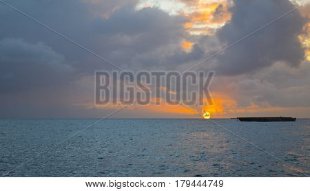Shadow of a barge at sea when the blazing orange sun touches the bleu Carribean water.