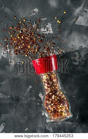 Plastic red pepper mill with scattered spices and salt in front of gray background