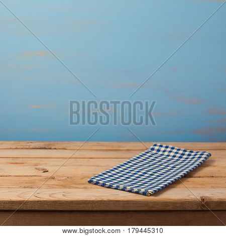 Empty wooden table with checked blue tablecloth over rustic painted wall. Kitchen background