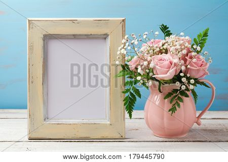 Poster or photo frame mock up template with rose flower bouquet in pink vase on wooden table