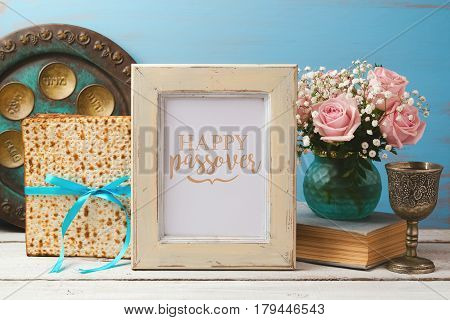 Jewish holiday Passover Pesah concept with poster photo frame matzoh and rose flowers bouquet