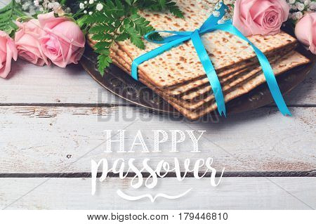 Jewish holiday Passover Pesah greeting card with matzoh and rose flowers over wooden background