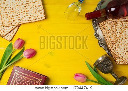 Jewish holiday Passover Pesah celebration with matzoh tulip flowers and wine bottle on yellow wooden background. View from above