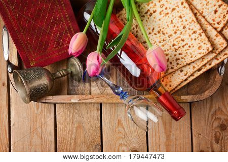Jewish holiday Passover Pesah celebration with matzoh tulip flowers and wine bottle on wooden background. View from above