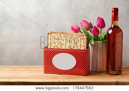 Passover celebration concept with wine bottle matzoh and tulip flowers over bright background