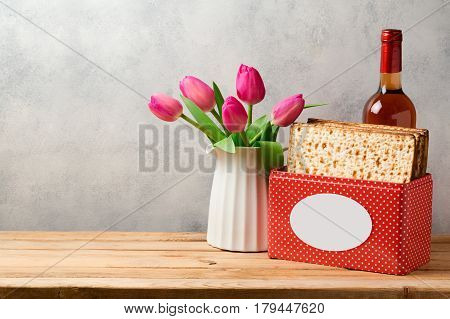 Passover holiday concept with wine bottle matzoh and tulip flowers over bright background