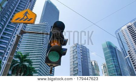 Green Traffic Light In The City With Yellow Cross Walk Street Sign And Urban Cityscape In Background