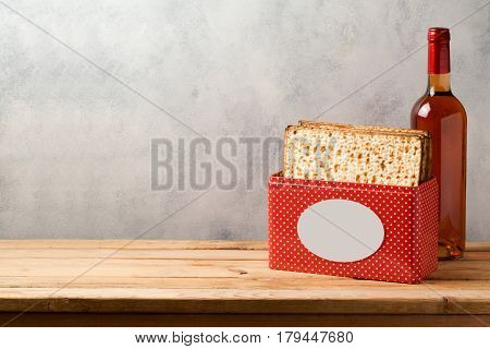 Passover celebration concept with matzoh and wine bottle on wooden table over bright background with copy space