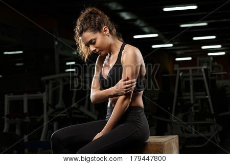 Image of serious strong sports lady sitting in gym and looking aside.