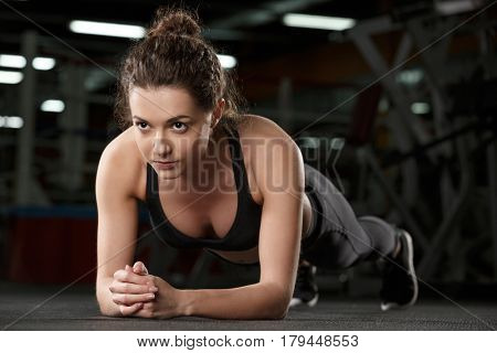 Picture of concentrated young strong sports lady make plank exercise in gym and looking aside.