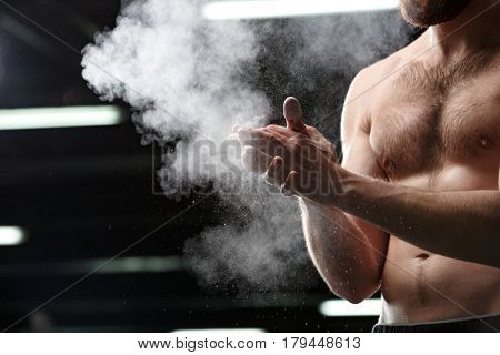 Cropped photo of handsome sports man in gym rubbing hands with chalk