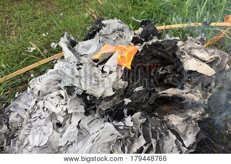 Burning Silver and gold paper and hat to worship ancestor in Chinese culture, the Qingming Festival at graveyard Cemetery