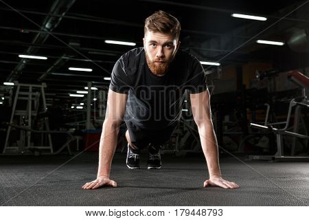 Picture of concentrated young strong sports man make plank exercise in gym and looking aside.