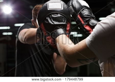 Image of concentrated handsome young strong sports man boxer make exercises in gym with trainer. Focus on trainer's hands.