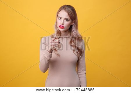 Image of confused young blonde lady with bright makeup lips pointing to camera over yellow background. Looking at camera.