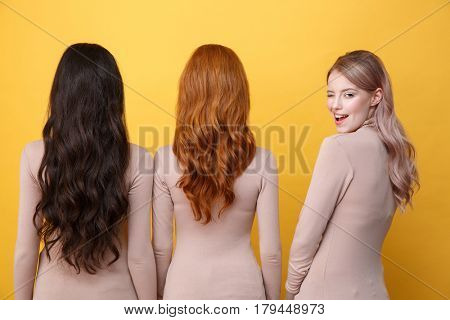 Back view picture of young three ladies standing over yellow background. Blonde cheerful lady winking to camera.