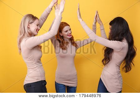 Photo of young cheerful three ladies standing over yellow background give a high five to each other.
