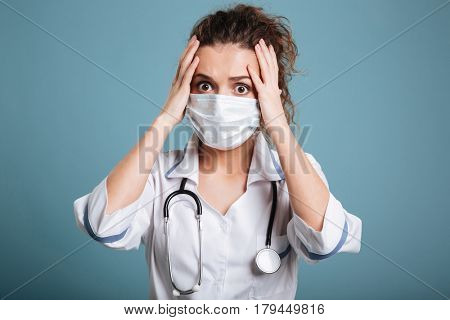 Suprised woman nurse in white lab coat standing and clutching her head isolated over blue background.