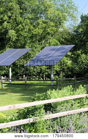 Two large solar panels collecting energy from the sun on a bright clear sunny day.