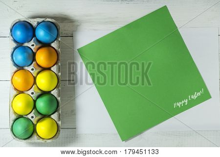 Easter eggs in a tray on a white wooden background. Top view with copy space