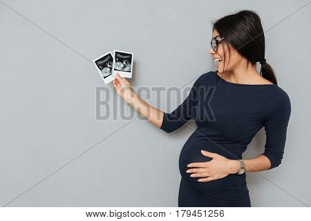 Picture of smiling pregnant business lady standing over grey background. Looking aside and holding ultrasound scans.