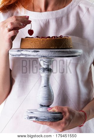 Woman's hands hold a cheesecake on a wooden cake stand.Cheesecake decorated with cherry sauce with berries