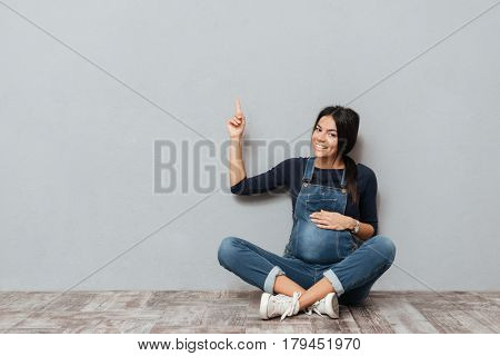Picture of smiling pregnant lady sitting on floor over grey background pointing to copyspace. Looking at camera.