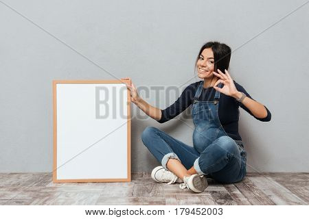 Photo of happy pregnant lady sitting on floor over grey background with copyspace desk showing okay gesture. Looking at camera.